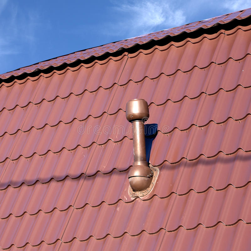 Roof of a house covered with metal tile with chimney stock photos