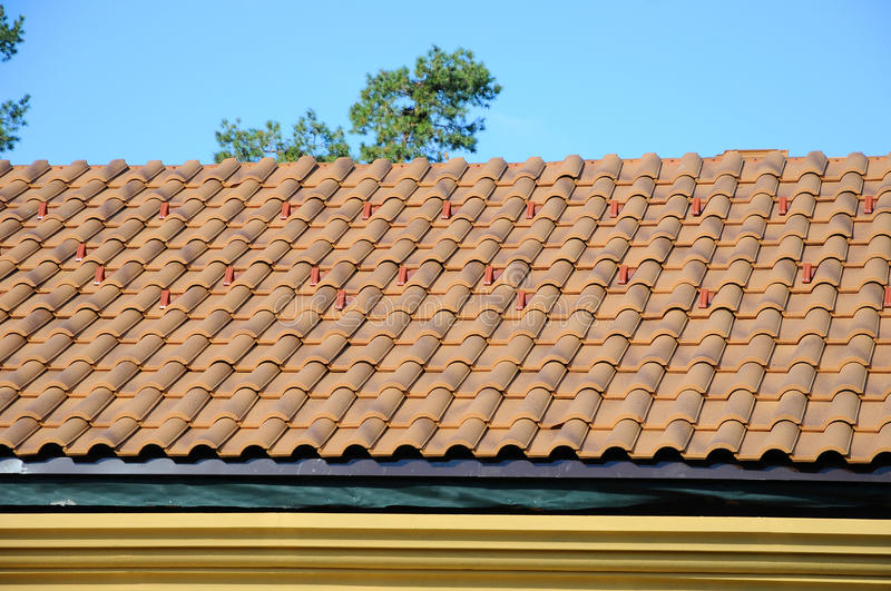 Roof house with tiled roof on blue sky. detail of the tiles and corner mounting on a roof, horizontal. roof protection from snow royalty free stock photos