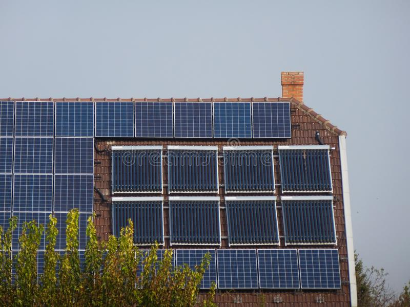 Roof installed PV solar panels and sun collector water heater pipe system royalty free stock image