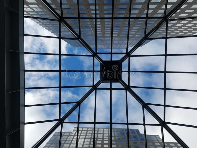 Through the roof, looking straight up through glass atrium roof at skyscrapers. royalty free stock image
