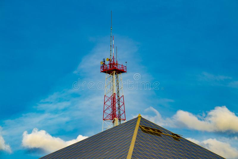 The roof of the office building and behind it a tall metal telecommunication tower. Front view royalty free stock photography