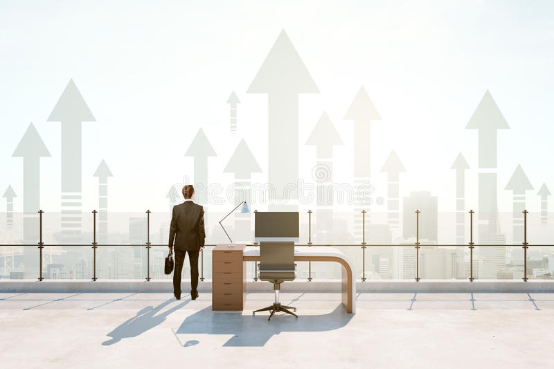 Roof office, success concept. Back view of businessman in abstract roof office with bright daylight and abstract upward arrows. Success concept royalty free stock images