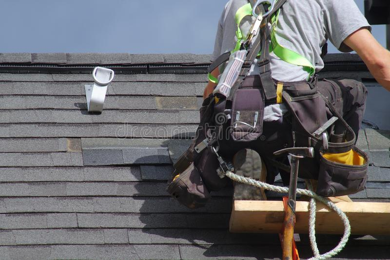 Roofer construction roof repair rope security worker royalty free stock image