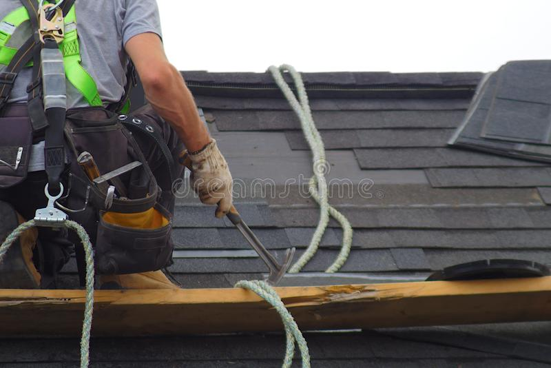 Roof repair construction worker roofer man roofing security rope. Roofer construction roof repair rope security worker royalty free stock photos