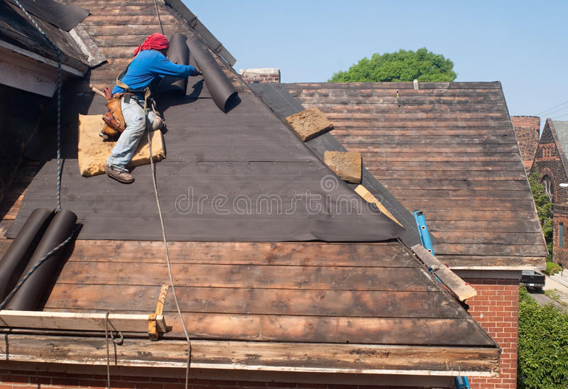 Roof Repair. Worker putting down tar paper on old historic house during roof replacement stock images