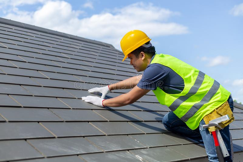Roof repair, worker with white gloves replacing gray tiles or sh stock images