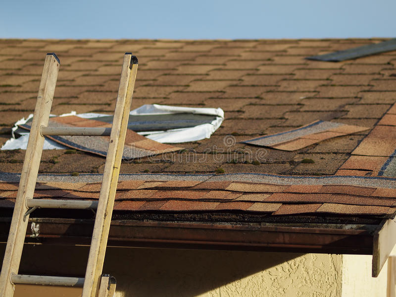 Roof replacement. Rooftop of residential building being fixed with new shingles royalty free stock image