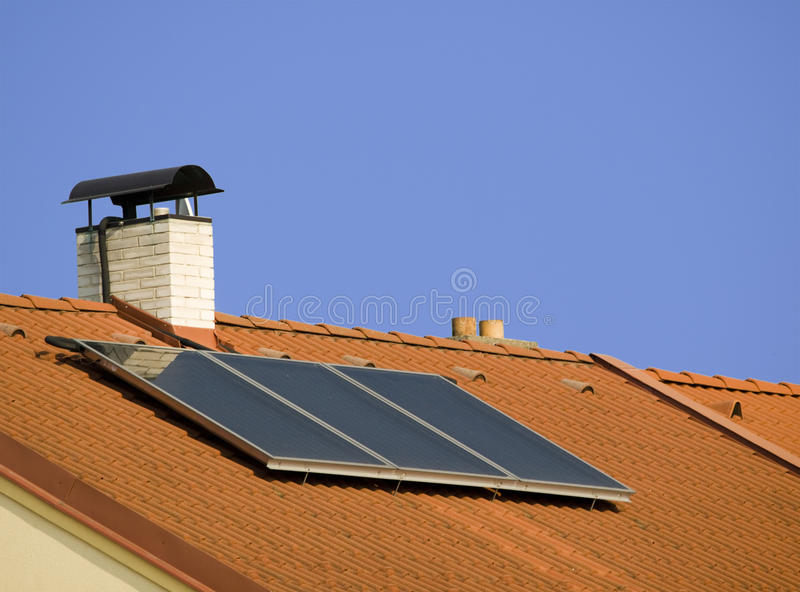 Roof with solar collector. Roof with white chimney and solar collector stock photo