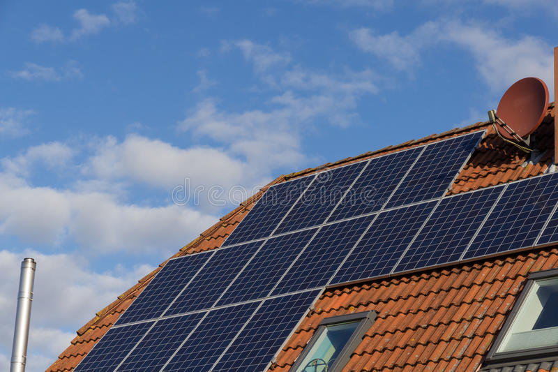 Roof with solar panels and blue cloudy sky stock photos