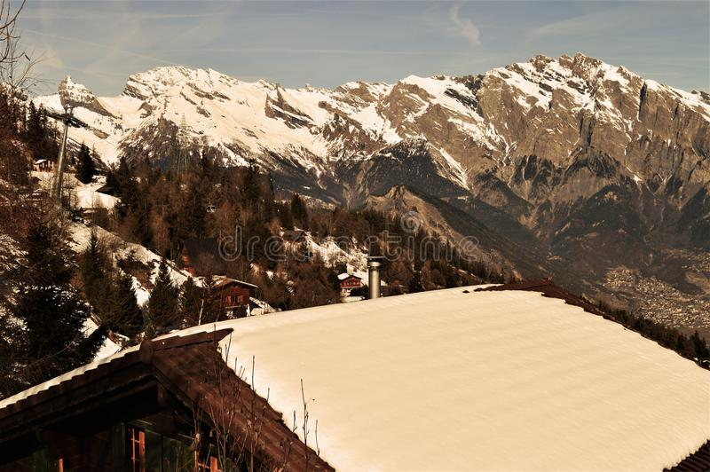 Roof and Swiss Alps. Roof under snow in the Swiss Alps which are high peaks, famous and touristic range of mountains in Switzerland. Beautiful serene landscape stock image