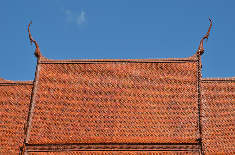 Roof of Thai temple. Orange,brown roof of Thai temple with blue sky royalty free stock image
