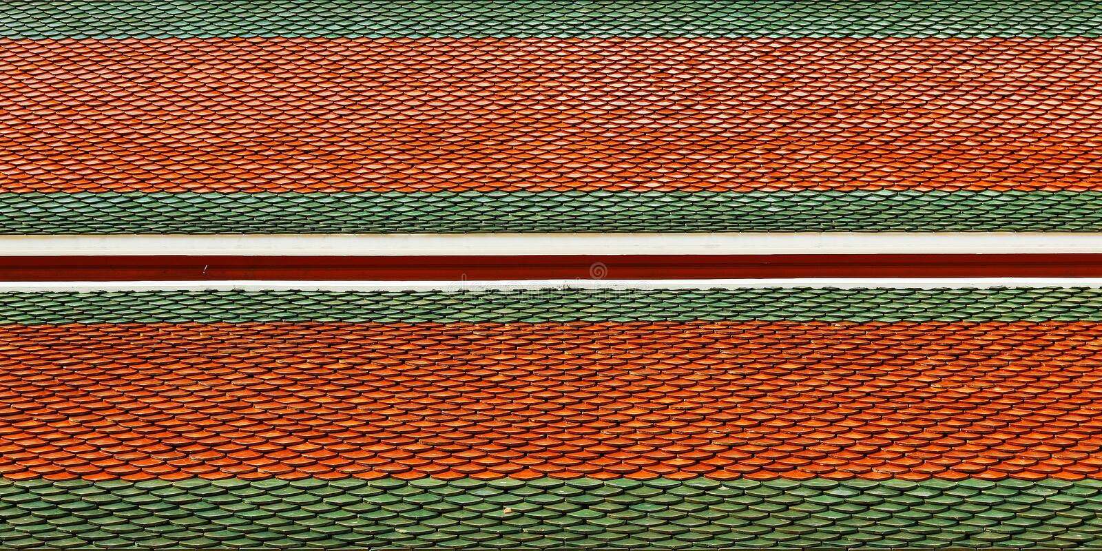 Roof tiles. Red and green on roof of Buddhist temple royalty free stock photos