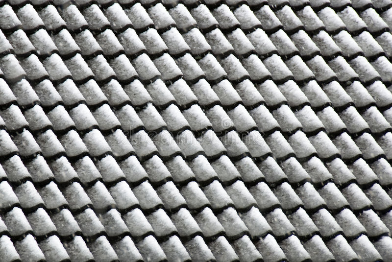 Roof tiles after snowfall. A view of roof tiles under a blanket of snow - after a snowfall royalty free stock photo