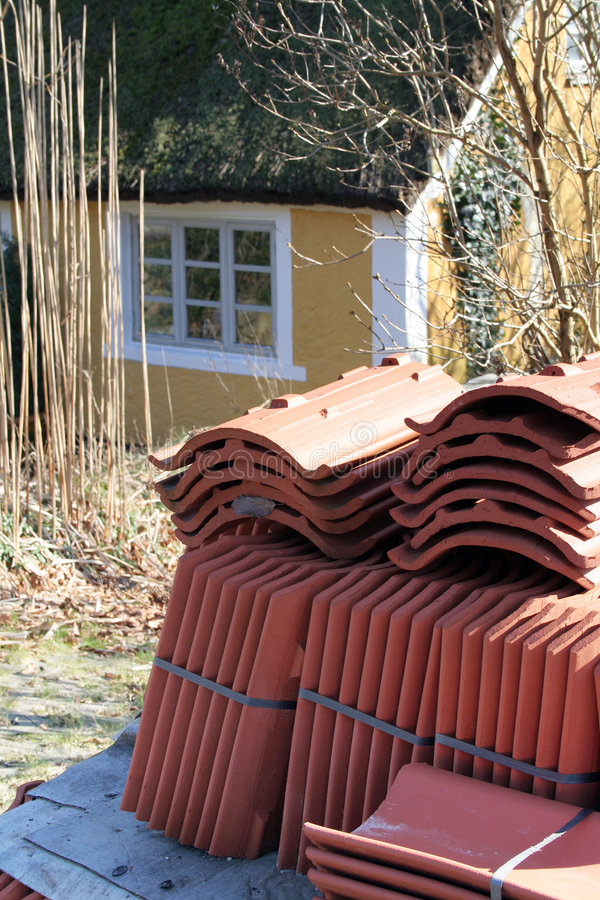 Roof tiles thatch. Roof tiles waiting to be laid on thatch cottage. stack of red tile by yellow house royalty free stock photography