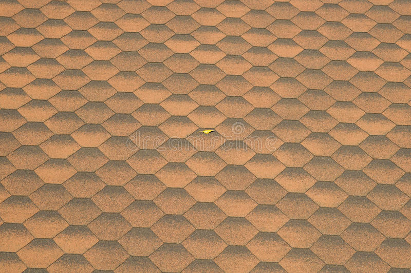 Roof tiles and yellow leaf. Regular pattern of hexagonal shape roof tiles of brown color and a single small yellow leaf in the middle of the surface. Distortion stock photos