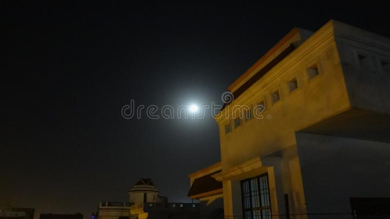 Roof top Lit by yellow street light on a full moon night. Even spread of yellow light on the structure. A full moon is visible in the dark skies in the royalty free stock image