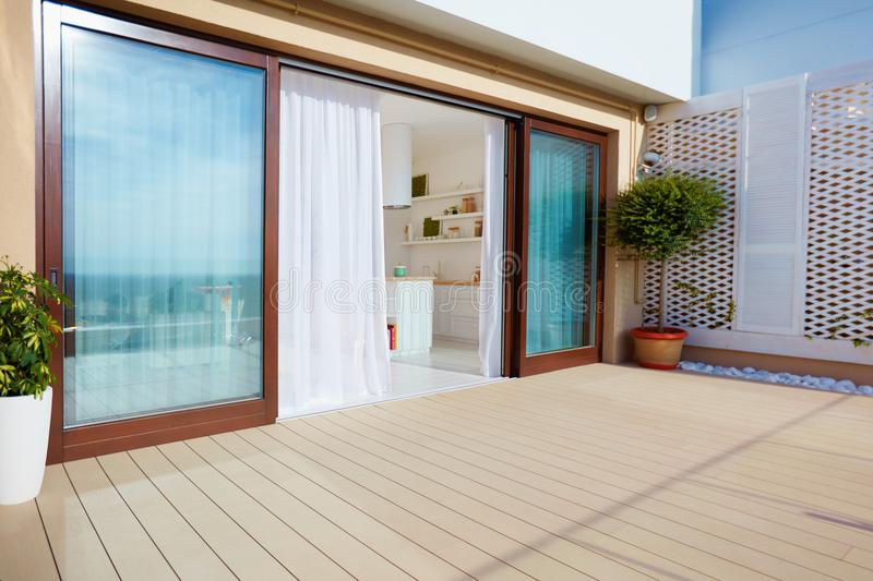 Roof top patio with open space kitchen, sliding doors and decking on upper floor. Roof top patio area with open space kitchen, sliding doors and decking on upper stock image