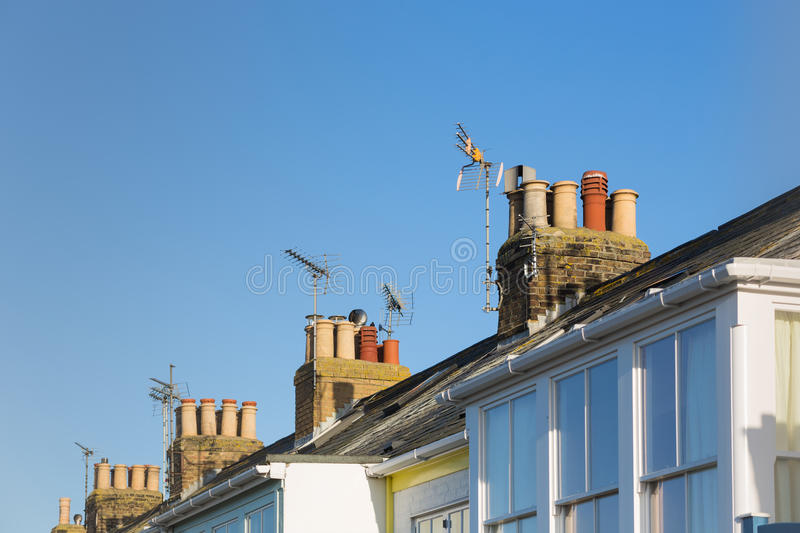 Roof tops with chimneys and TV aerials on terrace, row houses. Roof tops with chimneys and TV aerials on terrace, row houses, homes. against a blue sky stock image