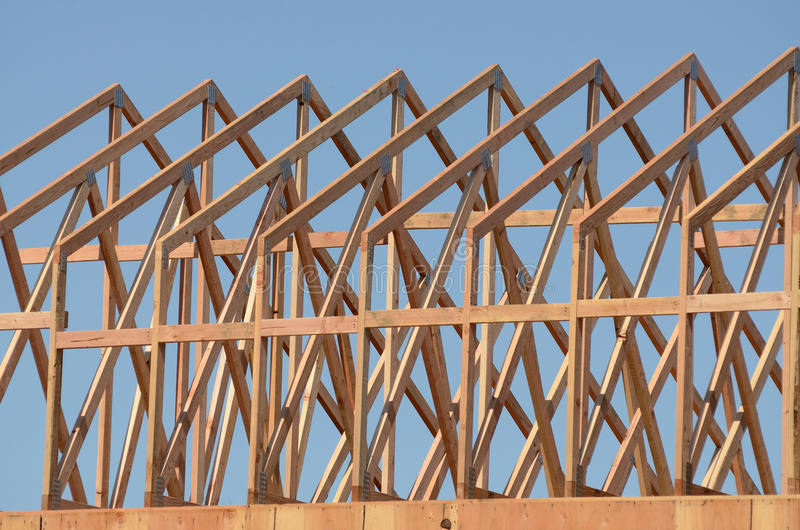 Roof Truss. Construction framing contractor installing the roof truss system to a new commercial residential development stock photography
