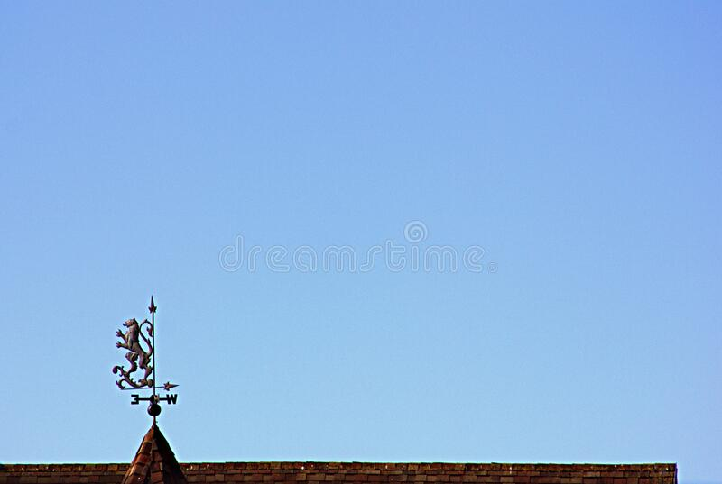 Roof and weather vane of a private house. Top of the roof of a private house with a weather vane in the summer at dawn in a minimalist style stock photos