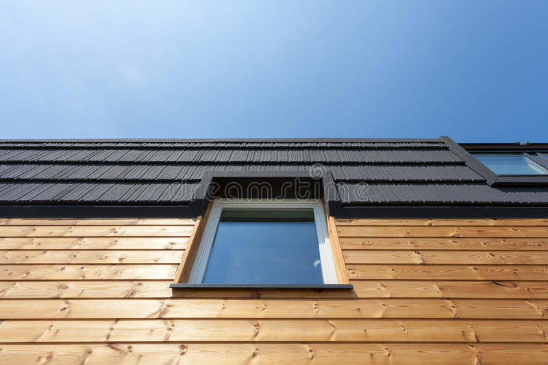 Roof Window on new wooden house against blue sky. stock photo