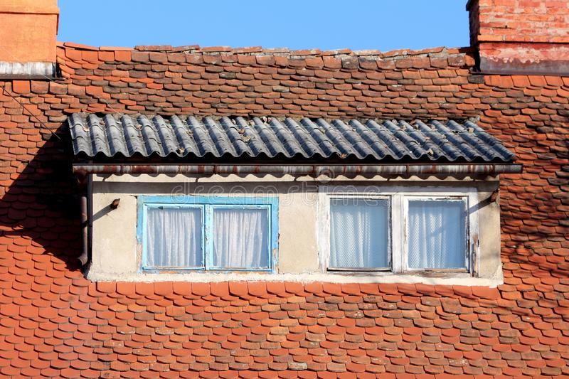 Roof windows with light blue and white dilapidated wooden frames surrounded with small roof tiles and rusted gutter next to two royalty free stock images