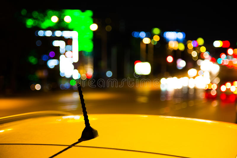 Roof of a yellow taxi cab in city at night stock image