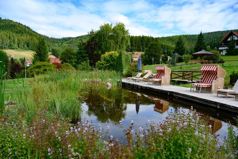 Bathing pond with gangplank, strandkorb, beach chair and blooming flowers and in small valley of Black Forest, Germany. Roofed wicker beach chairs with red and stock images