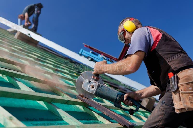 Roofer à l'aide d'une scie de circulaire de main photos libres de droits