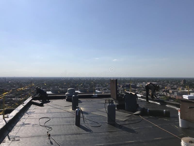 Roofer και ένα πλήρωμα που λειτουργεί σε μια ομαλή τροποποιημένη επίπεδη στέγη, πρόγραμμα υλικού κατασκευής σκεπής στοκ εικόνα