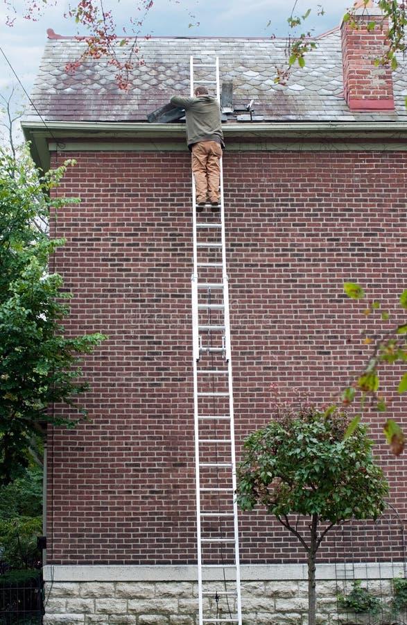 Roofer που αντικαθιστά την πλάκα στη στέγη στοκ εικόνες με δικαίωμα ελεύθερης χρήσης