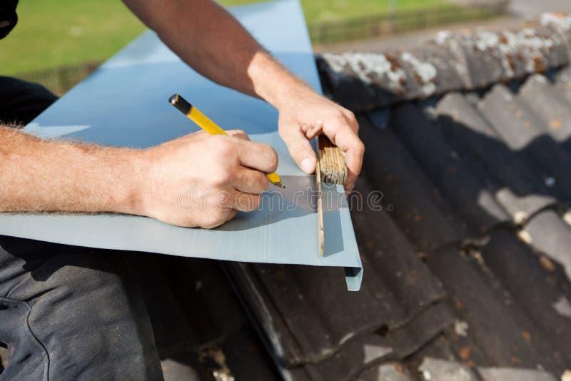 Roofer που μετρά και που χαρακτηρίζει ένα φύλλο μετάλλων στοκ φωτογραφία με δικαίωμα ελεύθερης χρήσης