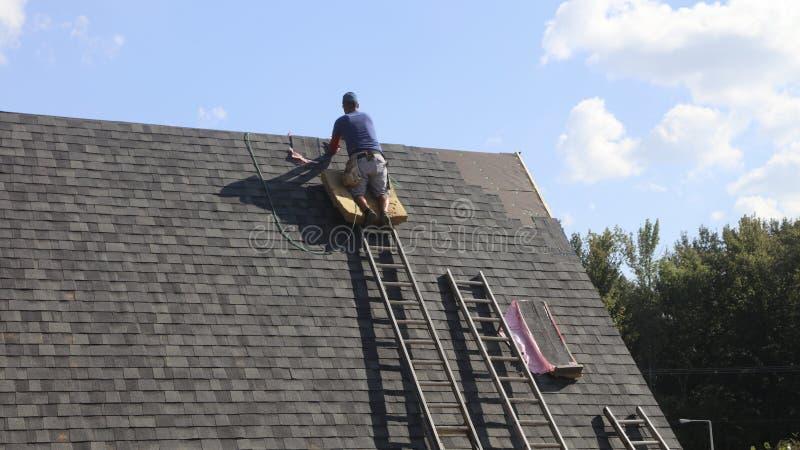 Roofer устанавливая крышу стоковое фото