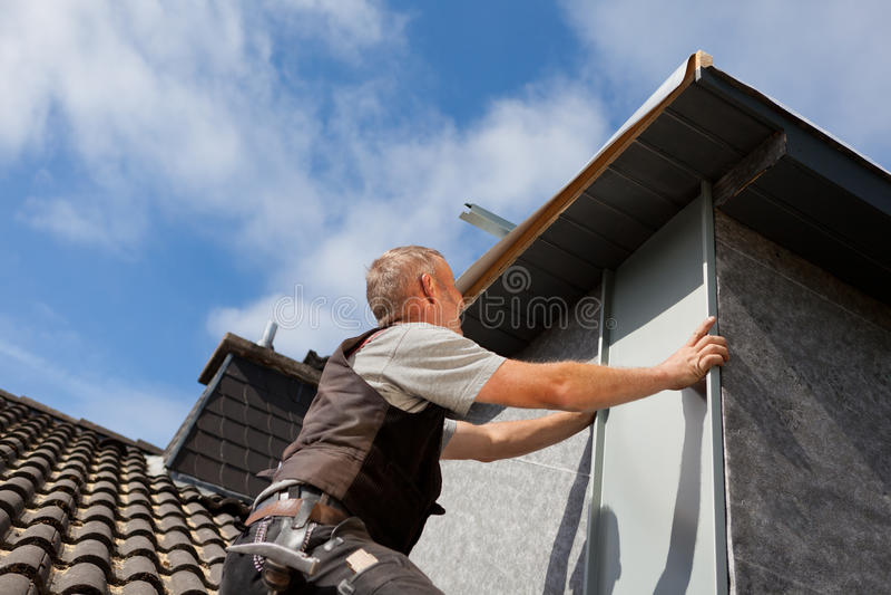 Roofer assembleert een metaalstuk in de koekoekmuur stock afbeeldingen