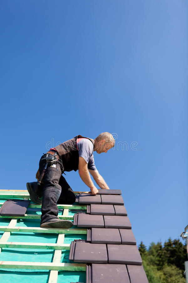 Roofer assembling gray tiles over the beams. On a sunny day stock photography