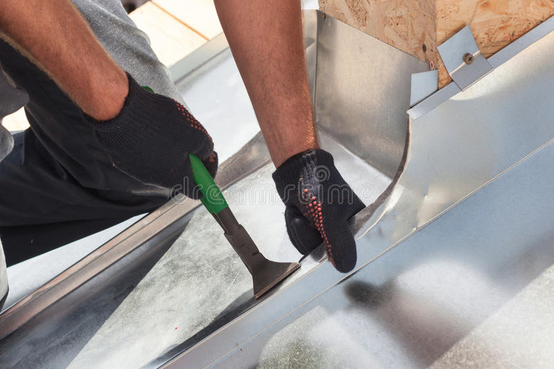 Roofer builder worker finishing folding a metal sheet using special pliers with a large flat grip. stock images