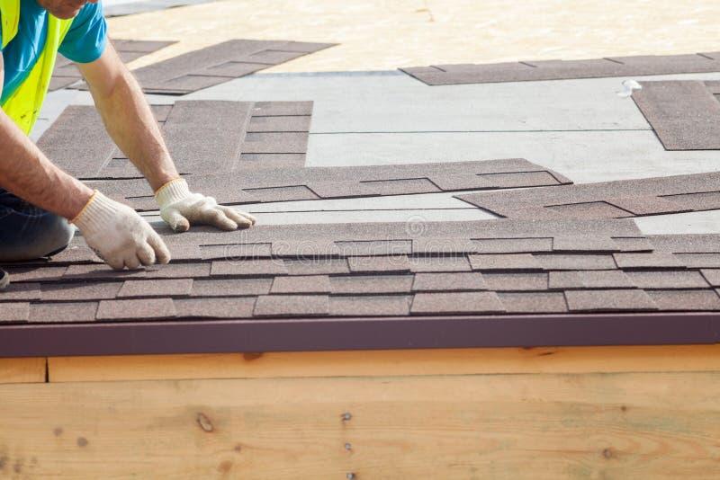 Roofer builder worker installing Asphalt Shingles or Bitumen Tiles on a new house under construction stock photos