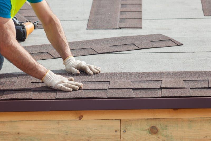 Roofer builder worker installing Asphalt Shingles or Bitumen Tiles on a new house under construction royalty free stock image