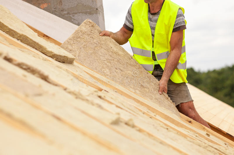 Roofer builder worker installing roof insulation material on new house under construction. royalty free stock images