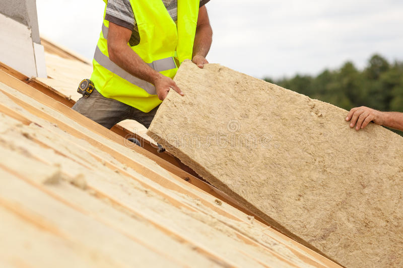 Roofer builder worker installing roof insulation material on new house under construction. stock image