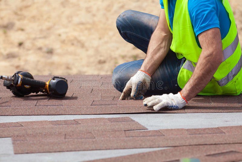 Roofer builder worker with nailgun installing Asphalt Shingles or Bitumen Tiles on a new house under construction. royalty free stock photo
