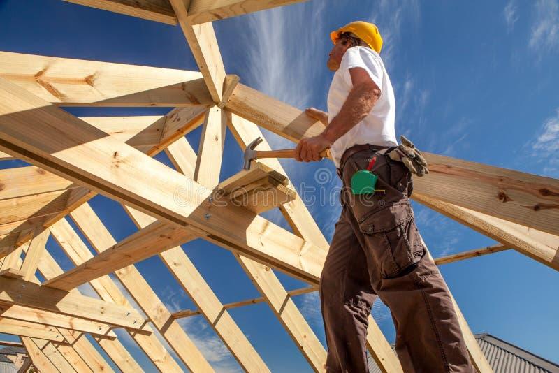 Roofer byggmästare som arbetar på takstrukturen av byggnad på konstruktionsplats fotografering för bildbyråer