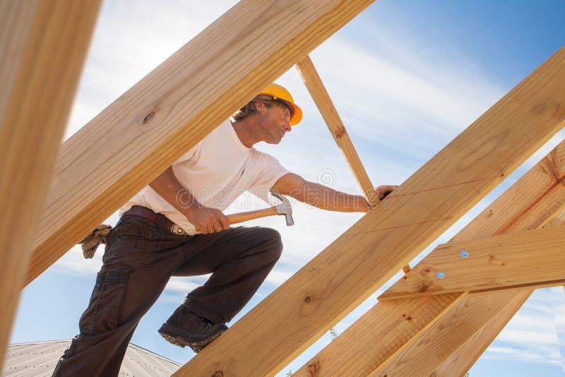 Roofer byggmästare som arbetar på takstrukturen av byggnad på konstruktionsplats royaltyfria bilder