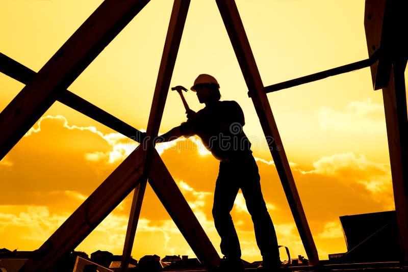 Roofer byggmästare som arbetar på takstrukturen av byggnad på konstruktionsplats royaltyfri bild
