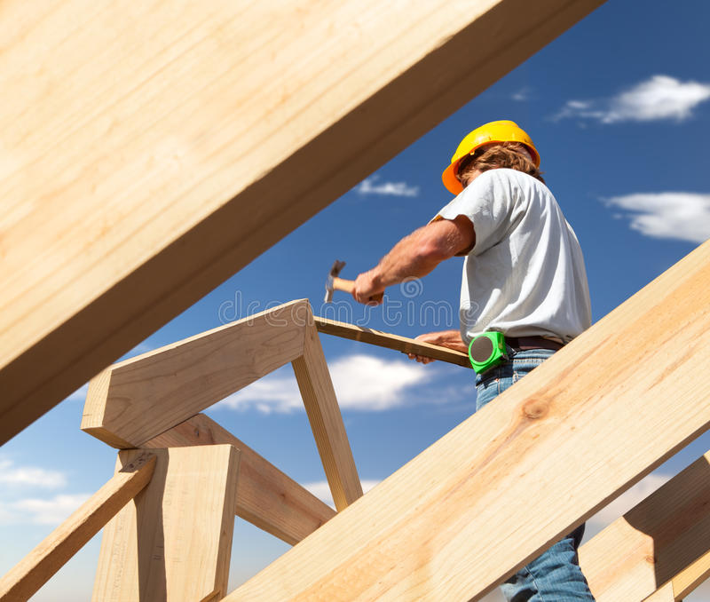 Roofer carpenter working on roof on construction site stock images