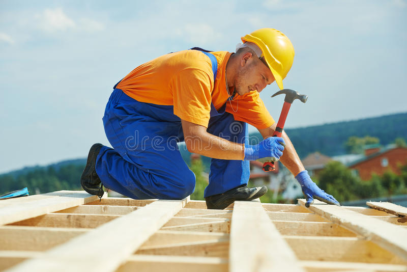 Roofer carpenter works on roof royalty free stock photo