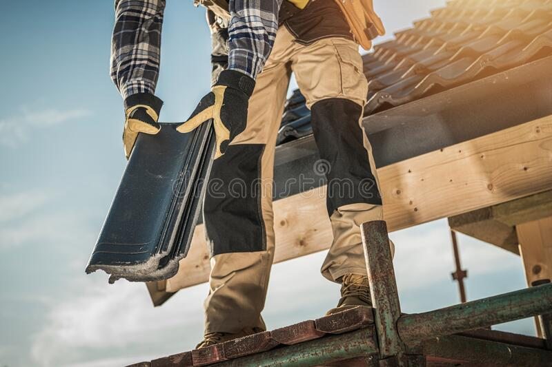 Roofer with Ceramic Tiles. Construction Industry. Roofer with Ceramic Tiles in Hands. Roof Worker Closeup. House Rooftop Covering stock photos
