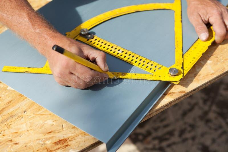 Roofer che lavora con un goniometro su una lamina di metallo fotografia stock