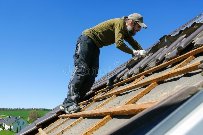 roofer che pone mattonelle sul tetto fotografia stock