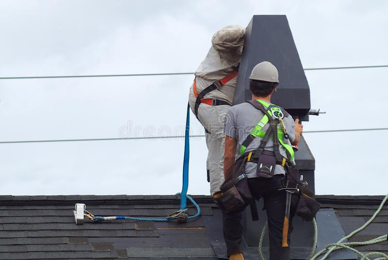 Roof repair construction worker roofer man roofing security rope royalty free stock photography
